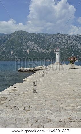 The artificially created island Our Lady of the Rock island in Kotor Bay Montenegro. A small oleander plant can be seen in the centre right and a small lighthouse in the background