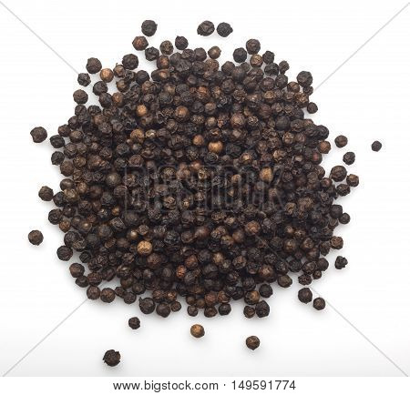 Pile of dried black peppercorns on white background