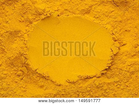 Pile of turmeric powder with center portion flat