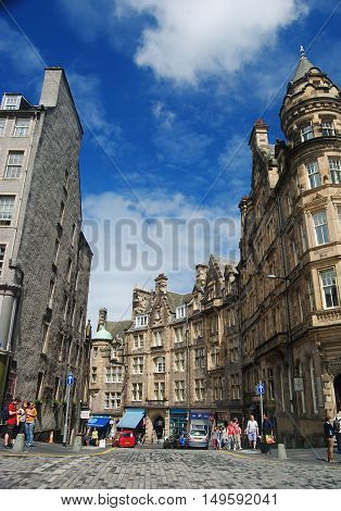 Edinburgh, United Kingdom - June 14, 2014. View of Cockburn St in Edinburgh, with historic buildings, commercial properties, shop windows, cars and people.