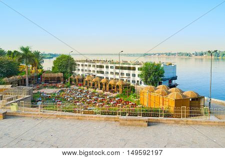 The cruise liner at the bank of Nile in Kom Ombo with the view on luxury restaurant complex surrounded by greenery Egypt.