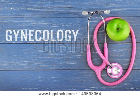 Gynecology concept. Stethoscope with apple on wooden table