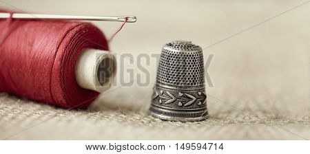 Old needle thread and thimble - website banner of hobby hand-made concept