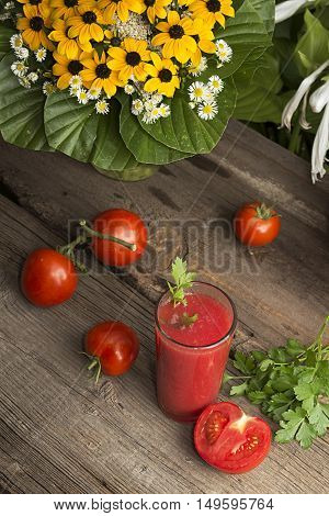 Glass of tomato juice and fresh tomatoes on old wooden table decorated with yelow flowers. Rustic style