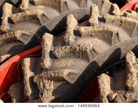 Close up of tractor tire wheel with soil dirt - great agriculture background image