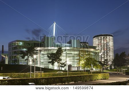 WOLFSBURG GERMANY - SEP 23 2016: Contemporary buildings at the Volkswagen Autostadt illuminated at night. Wolfsburg Germany