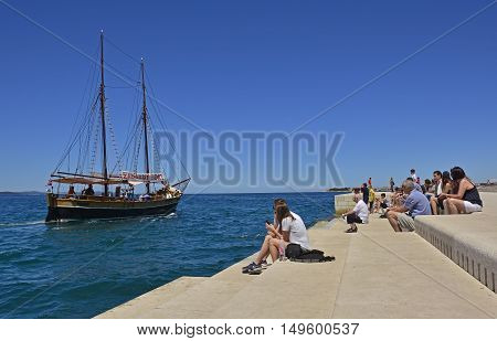 Zadar Croatia - June 18th 2016. Tourists watch the boats go by as they listen to the Sea Organ (Morske Orgulje) on zadar's waterfont. This experimental musical instrument plays music through the movement of sea waves and tubes positioned under the steps.
