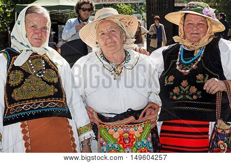 TIMISOARAROMANIA - SEPTEMBER 242016:Group of three old Romanian women dressed in folk costumes present at a fair with traditional products Fair of craftsmen