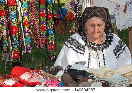 TIMISOARA ROMANIA - SEPTEMBER 24 2016: Old romanian woman who sells traditional products at a fair called Fair of craftsmen