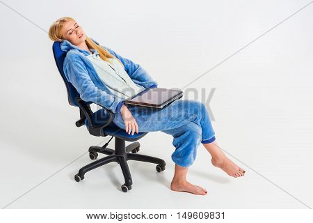 girl in pajamas with a laptop. studying or doing online shopping. work from home. tired of sleeping in a chair