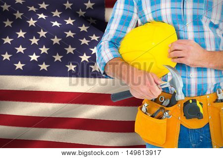 Manual worker wearing tool belt while holding hammer and helmet against close-up of american flag