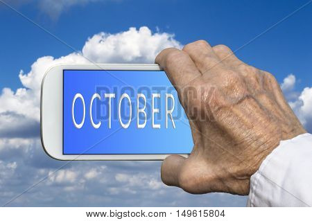 Smart phone in old hand with month of the year - October on screen. Selective focus.