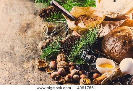 Christmas or New Year baking cake background. Dough dough ingredients - flour chocolate walnuts hazelnuts sugar eggs cinnamon and Christmas decorations on wooden rustic background