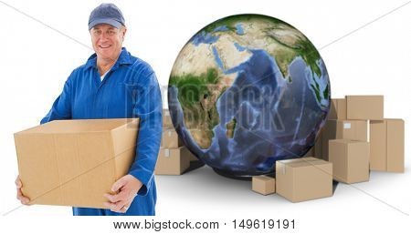 Happy delivery man holding cardboard box against globe amidst cardboard over white background