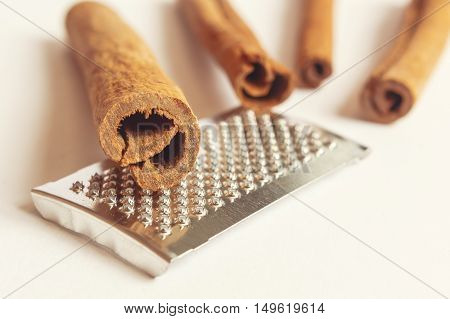 Close-up of fragrant cinnamon sticks and grater. Selective focus.