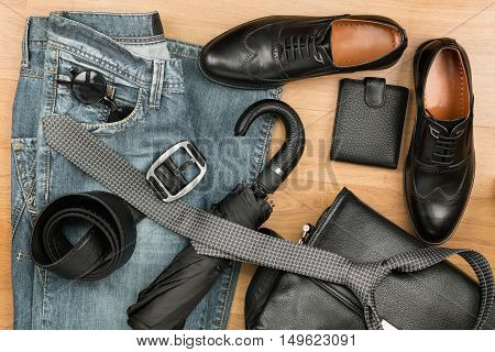 Classic black shoes and men's clothes and accessories lie on the wooden floor can be used as background top view