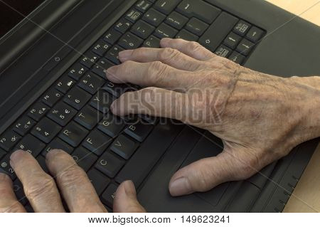Closeup on elderly hands on keyboard of laptop. Selective focus.
