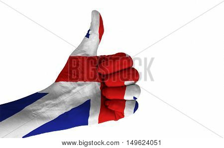 Hand with thumb up gesture in colored United Kingdom national flag isolated on white background.