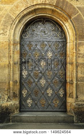 Old door on St Vitus Cathedral at Prague Catsle Hradcany Czech Republic. Side entrance in Castle.