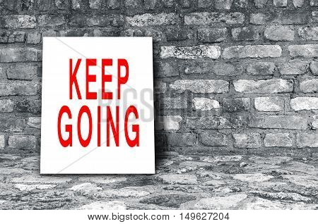 Keep Going sign on floor in black interior