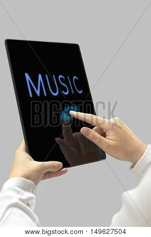 Music message on digital tablet computer display. Woman hands with tablet computer. Selective focus.