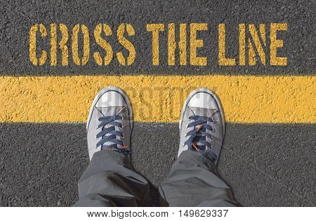 Sneakers standing on the yellow line. Crossing line concept.