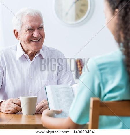 Retiree And Nurse Reading Book