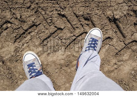 Top view of sneakers on a very dry terrain.