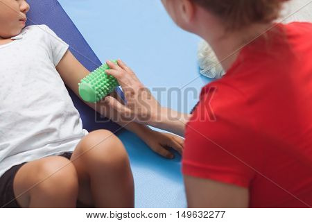 Shot of a therapist using a roll massage on a little girl's arm during a therapy