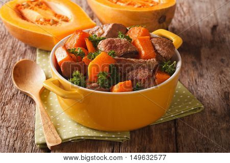 Braised Beef With Pumpkin, Onion And Spices Close Up In A Yellow Pan. Horizontal