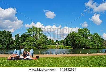 London, Great Britain - May 14, 2014. Grass lawn in Kensington Gardens with a couple lying on the grass, and six-metre high Roman travertine sculpture The Arch is visible across the Long Water.