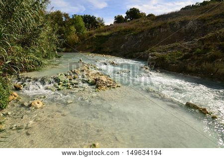 Thermal hot springs with tiny waterfalls in Tuscany Italy.