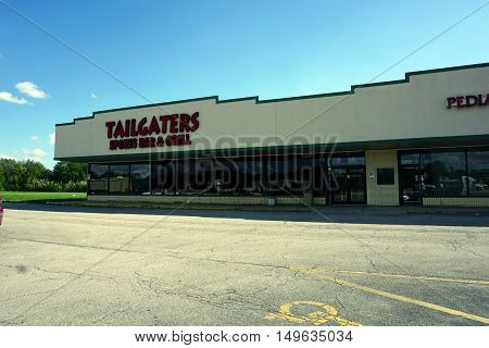 BOLINGBROOK, ILLINOIS / UNITED STATES - SEPTEMBER 17, 2016: One may drink beer at the Tailgaters Sports Bar and Grill, in Bolingbrook's River Woods Plaza strip mall.