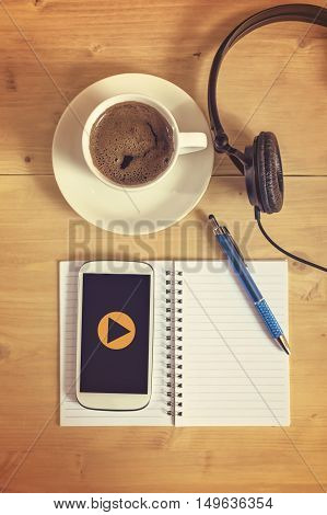 Play button on smart phone with headset notebook pencil coffee cup on wooden table business concept. Selective focus.