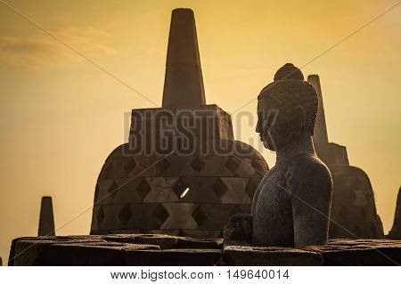 Buddha statue in open stupa in Borobudur or Barabudur temple Jogjakarta Java Indonesia at sunrise. It is a 9th-century Mahayana temple and the biggest Buddhist Temple in Indonesia.