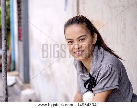 Portrait asian woman relaxing at market street. Close up face of happy woman looking at camera. Portrait of a smiling woman with a tan or honey-colored skin.