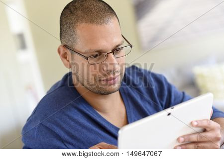 Man with eyeglasses and blue shirt websurfing on tablet