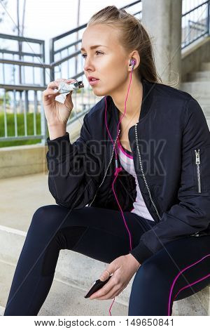 Sporty young woman eating protein bar while listening music on steps