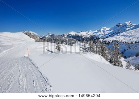 View ti Skiers on the ski slopes and Swiss Alps covered by fresh new snow seen from Hoch-Ybrig ski resort Central Switzerland
