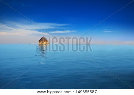Overwater bungalow in blue tropical lagoon near Maldives island