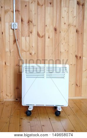 Working white electric convector heater plugged to power line in a wooaden house room front view closeup