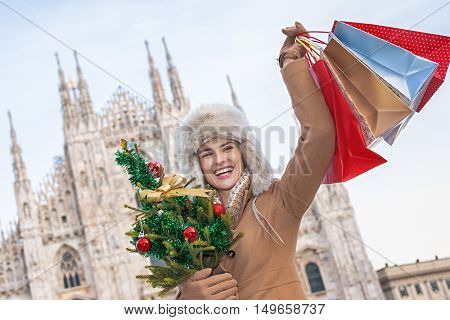 Woman With Christmas Tree And Shopping Bags In Milan Rejoicing