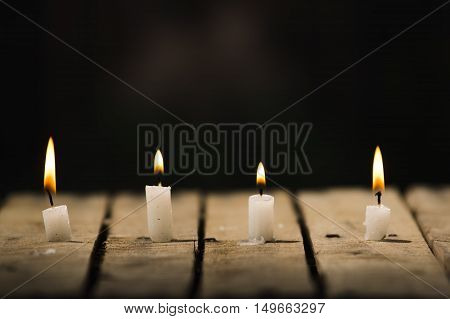 Four white wax candles sitting on wooden surface burning with black background, beautiful light setting.