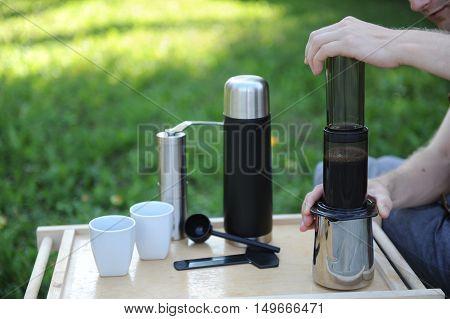 Man making fresh aeropress coffee in nature