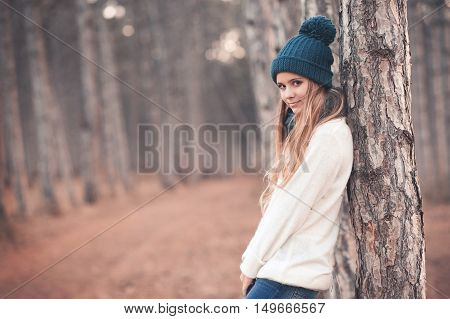 Stylish teen girl 14-16 year old wearing white knitted sweater and blue knitted hat posing in forest outdoors. Looking at camera. Winter season.