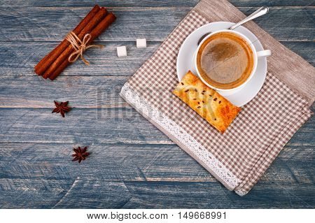 Cup of hot morning coffee on saucer with sugar. Spoon. Vanilla sticks and star anise wooden board in rustic style