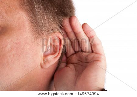 Close up of a deaf man's ear with hearing aid cupping his hand behind his ear. Isolated on white.