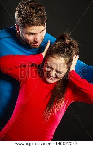 Husband abusing wife. Aggresive man screaming at crying scared woman. Domestic violence aggression.