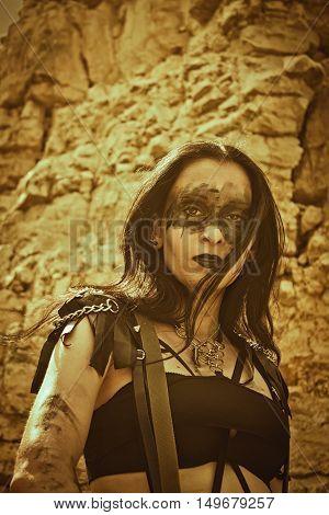 Pretty dirty post-apocalyptic warrior posing over rocks
