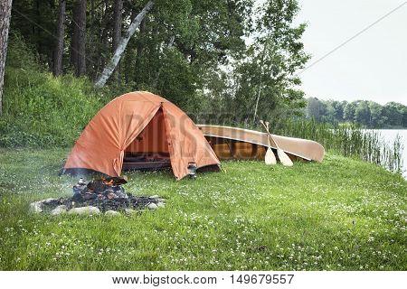 An orange tent a campfire and canoe on Minnesota lake